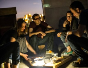 Campers talk and share food on an undisclosed rooftop